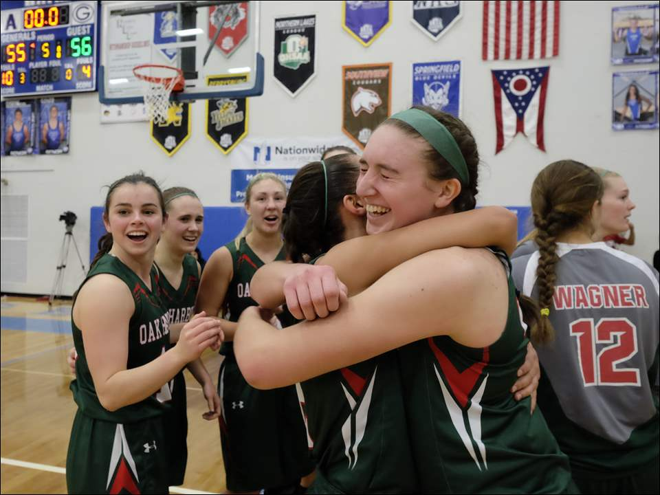Oak Harbor players Sophia Eli and Ashley Riley, right, hug after the Rockets defeated Rogers.