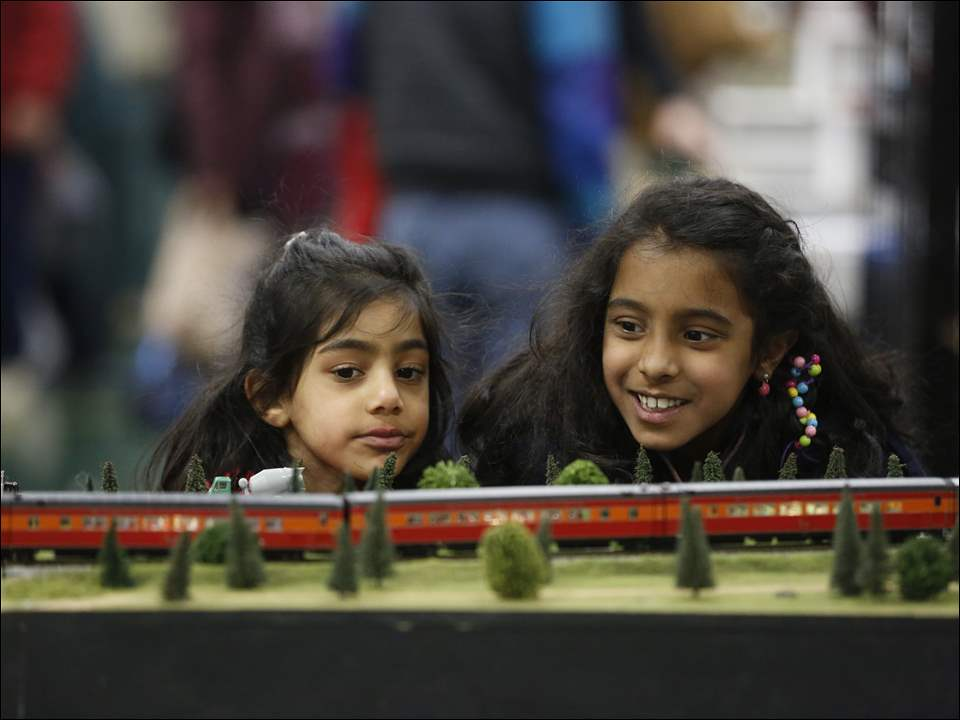 Sisters Hareem Qureshi, 4, left, and Suniya Qureshi, 7, right, of Sylvania, look at a model train during the Greater Toledo Toy & Train Show at Owens Community College in Perrysburg.