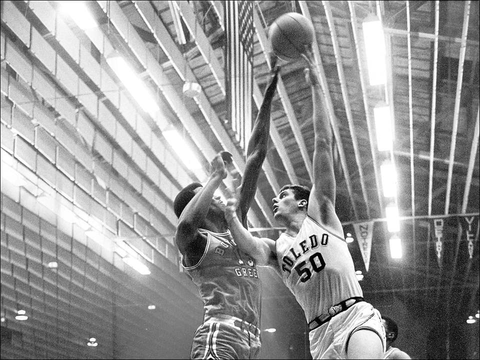 The University of Toledo and Bowling Green State University met on Jan. 3, 1968, in MAC tournament play. Blade photographer Don Strayer was courtside for the action and snapped this photo of UT's Steve Mix trying to go up and over Falcons player Albert Dixon at the UT Fieldhouse. UT won in overtime, 73-69, before a crowd of 4,118.  Mix is arguably the best player to put on a Rockets jersey. A Rogers High School graduate, Mix decided to play college basketball for his hometown team. In three seasons — freshmen could not play on the varsity team then — he played in 73 games, scored 1,676 points, and had 872 rebounds. He earned All-MAC honors three times and was the league's first Player of the Year. He was the third Toledo player to earn All-American honors. Mix was drafted by the Detroit Pistons and played 13 seasons in the NBA with Detroit, Los Angeles, Denver, and Milwaukee. He was with the Philadelphia 76ers for the longest time, from 1973-1982. Mix and his wife, Maryalice, called Toledo home until about a year ago, when they moved to Florida  Albert Dixon, Jr., also a Toledo native, played at Scott High School before enrolling at Bowling Green State University. While at BGSU, he tied former player Nate Thurmond's record of 31 rebounds in a single game. He was a third-round draft choice for the Kentucky Colonels in the old American Basketball Association and was drafted by the Baltimore Bullets in the NBA. But he chose to play with the Harlem Globetrotters rather than join a professional league. Dixon played for the Globetrotters for about a year, and then taught in the Toledo public schools in the early 1970s. He also taught school in the Detroit area. He died in 2001.