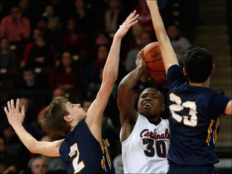 Cardinal Stritch's Joey Holifield (30) is guarded by Archbold's Bryce Williams (2) and Rigo Ramos (23).