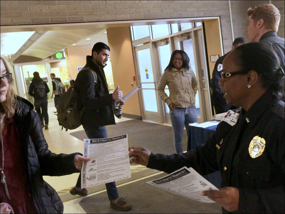 As Alyan Memon, top center left, flashes a thumbs-up to University of Toledo Police Chief Jeff Newton, top right, Lt. Tressa Johnson, bottom right, hands a flyer on safety to Justine Clark, left. The University of Toledo police host a booth at UT's student union monthly to hand out informational flyers and distribute free slices of pizza.