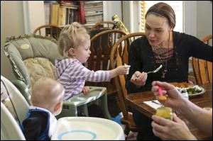 Tiffanie Howell feeds her 15-month-old daughter Kensingtyn at the Aurora Project Inc. house in Toledo. Aurora Project gets $76,296 in federal block grant funds.