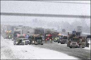 Crews work to untangle a 21-vehicle pileup on northbound I-75 north of State Rt. 582 in Wood County. Three people were hurt seriously and three suffered minor injuries Friday.