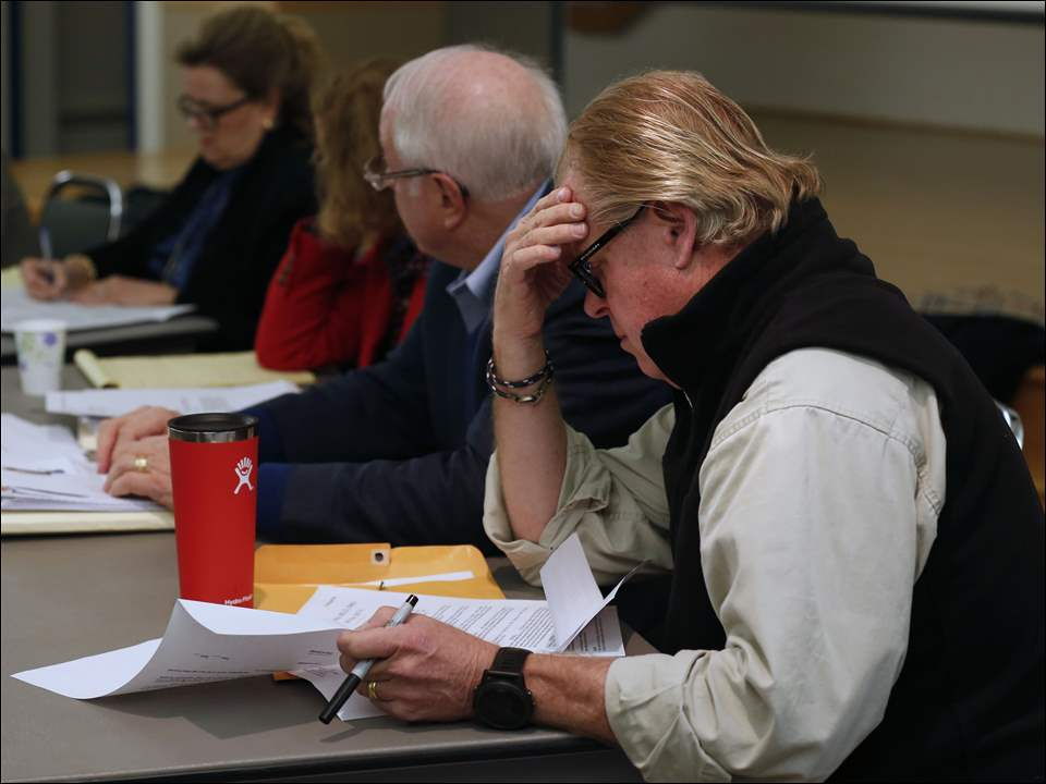 Ottawa HIlls Councilman Jeffrey Gibbs, right, reads documents on the Secor Road expansion during a council meeting at the Hope Lutheran Church. Gibbs opposed the project and the council voted 4-2 not to move forward with construction.