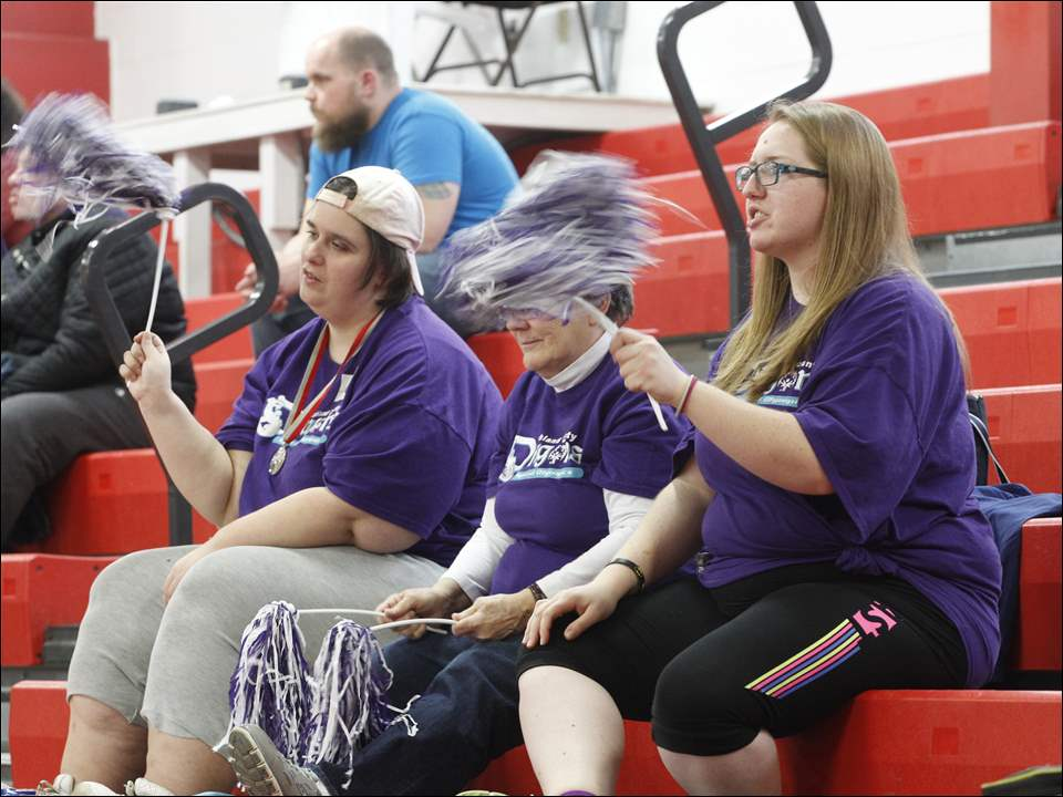 Carol Brown, left, Durita Kirby, and Ashely Shepard, all of Ashland County, supporting Ashland County athletes who are performing on four different courts in front of them at the Special Olympics Ohio state basketball tournament skills contest.