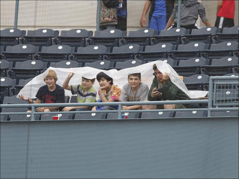 Students attending Thursday morning's game at Fifth Third Field between the Toledo Mud Hens and Charlotte Knights wait out a rain delay, which began just before the fourth inning and lasted 37 minutes. The Knights defeated the Mud Hens, 6-5.