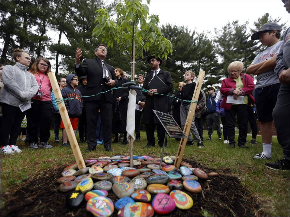 Cantor Ivor Lichterman, left, and Rabbi Evan Rubin, right, perform a cermony around a newly planted horse chestnut tree during Yom HaShoah: A Musical Reflection at  the Temple Shomer Emunim in Sylvania Township.