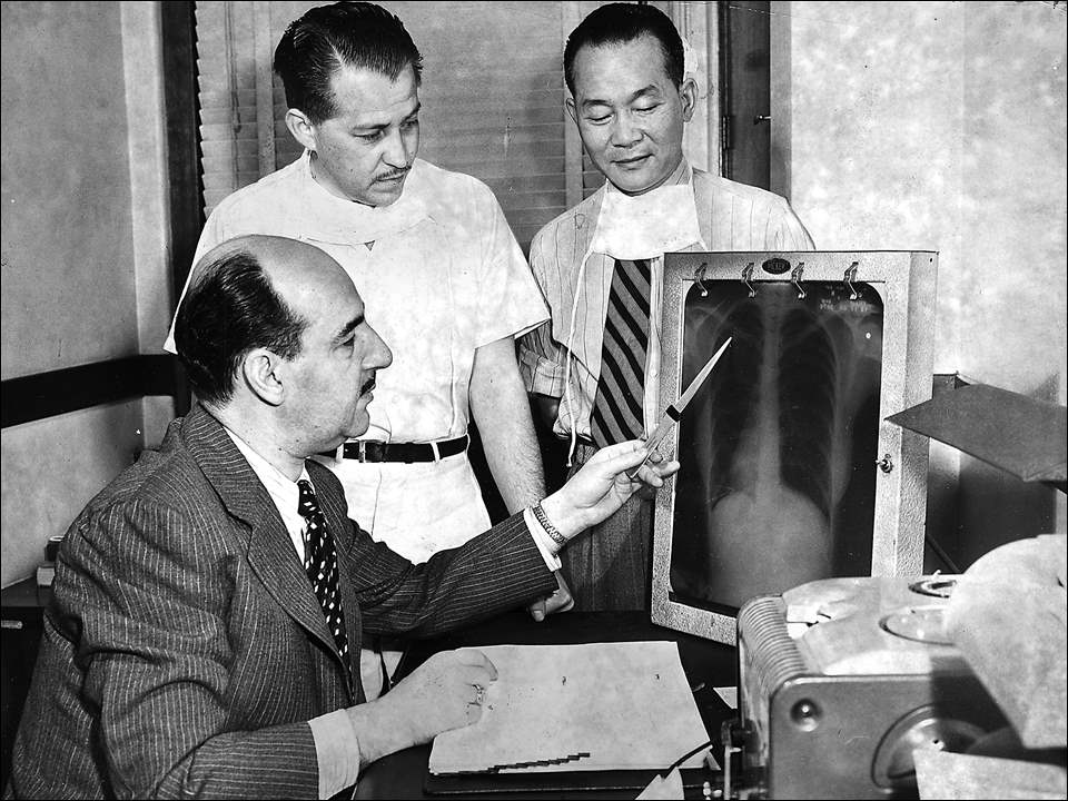 "This Blade archive file photo, dated May 23, 1950, shows Dr. Phillip Cohn, left, and assistants, Dr. Jose Siero and Dr. Jack Wu, looking at a chest X-ray at the William Roche Memorial Hospital in Toledo.  The facility was referred to as a tuberculosis hospital and was having difficulty finding trained American chest doctors on its available budget. Few doctors specialized in chest diseases because of the comparatively low pay, making it necessary to hire foreign doctors. But Dr. Siero, from Nicaragua, and Dr. Wu, from China, were ruled ineligible to be staff physicians at the Roche Hospital.  The Ohio Civil Service commission determined that the two men could not be doctors at the facility because state law required staff members of a county institution to be both U.S. citizens and graduates of a Class A medical school eligible to be licensed in Ohio.  To get around the ruling, the hospital board designated the two men as ""medical secretaries"" reporting to Dr. Cohn, who was the hospital superintendent. The medical secretary position was a classification exempt from civil service oversight.  The hospital planned to ask other tuberculosis hospitals to join them in Columbus to address state lawmakers and ask to have the rules changed.  William Roche Memorial Hospital was funded by a 0.3-mill real estate tax levy. On average, it had 183 patients."