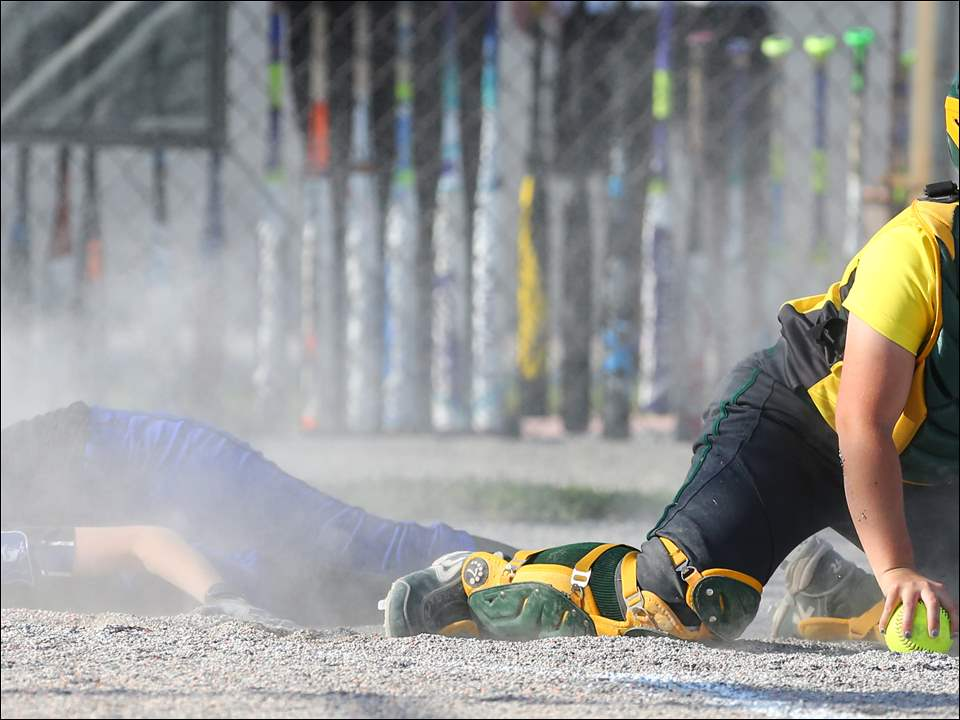 Springfield second baseman Jo Reuling (4) scores against Oregon Clay catcher Natalie Quinlan (5) during a Division I district semifinal softball game  at Rolf Park  in Maumee, Ohio.