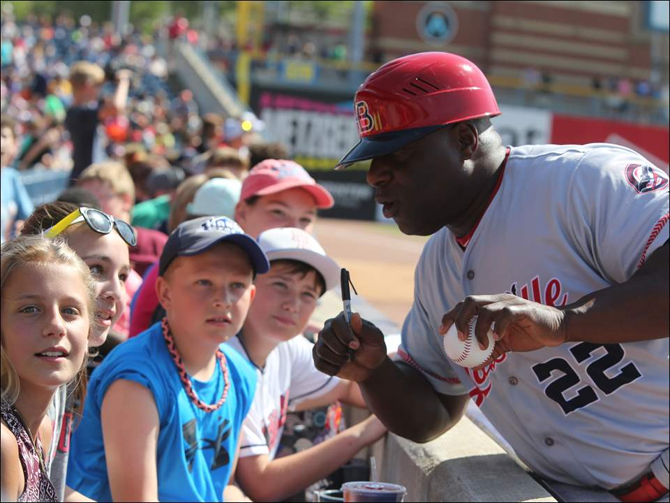 Louisville Bats bench coach Darryl Brinkley signs an autograph for Jenna Ritchie, left. Also pictured is Pierson Steyer. They are both sixth graders at Old Fort Elementary School.