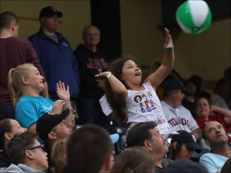 A young Toledo Mud Hens fan hits a beach ball during a rain delay against Scranton/Wilkes-Barre Sunday.