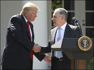 President Donald Trump shakes hands with EPA Administrator Scott Pruitt after pulling the United States from the Paris climate change accord.