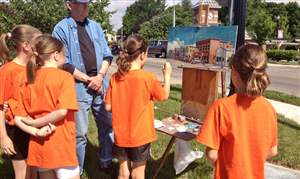 Waterville-Plein-Air-Artist-Jim-White-allows-children-to-add-their-own-touch-to-his-painting-of-Third-St-jpeg