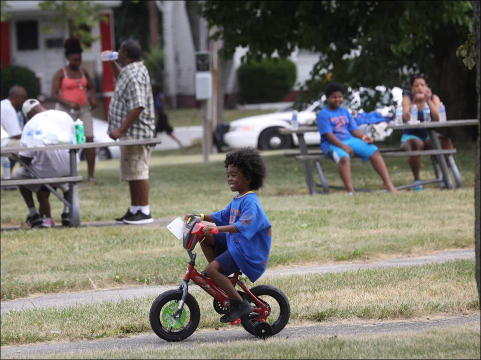 Harold Young IV, 5, center, takes a donated bike for a spin before the drawing at Smithfest.