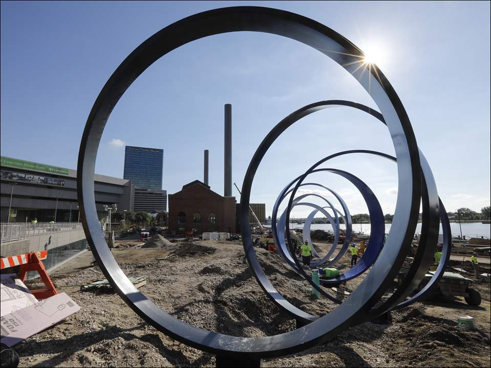 Workers from Canaan Construction install Echo, the ringed sculpture that was created by local artists out of the reclaimed smokestacks from the former steam plant.