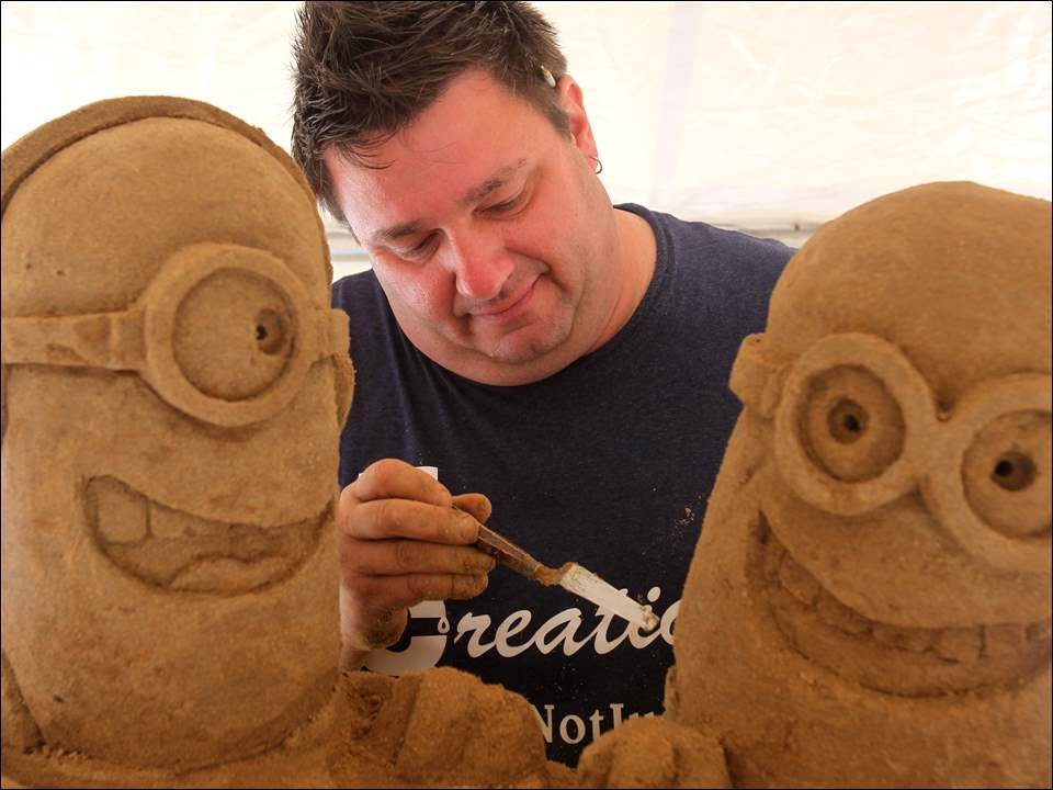 Danny Kissel of Shippensberg, Pa., works on details of his 'Despicable Me' sand sculpture.