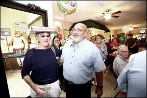 Frank Incorvaia, Jr., co-owner of Inky's Italian Foods, laughs at Nancy Cryderman, as the two have fun during a 60th anniversary pizza party attended by friends and family.