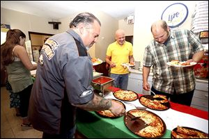 Steve Pahle, left, Gary Jones, center, and Tom Dennis, dig in as pizza and other Italian dishes were offered to friends and family in celebration for Inky's Italian Foods still being in business after opening  its doors in 1957.