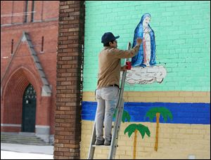 Artist David Cuatlacuatl paints a figure representing the Immaculate Conception on a mural at The Immaculate Conception Church outreach center June 7.  Mr. Cuatlacuatl was killed in a head-on crash on Thursday.