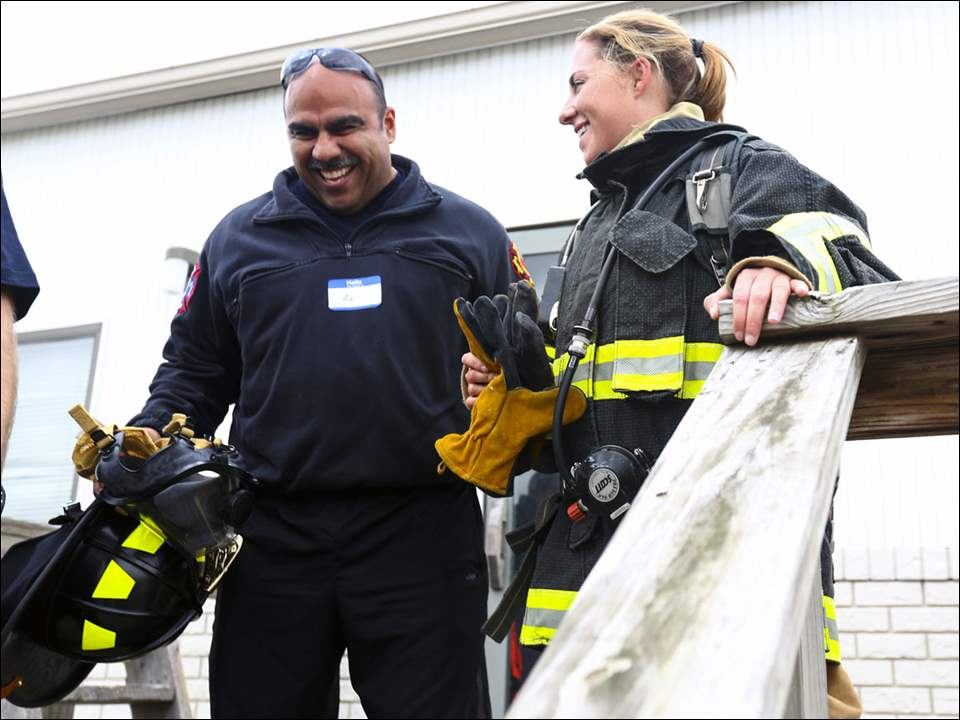 Blade reporter Allison Reamer, right, and her trainer Toledo Firefighter Al Campos, left, laugh together after Reamer participated in an exercise during Toledo Area Fire Ops at Owens Community College on September 8, 2017.