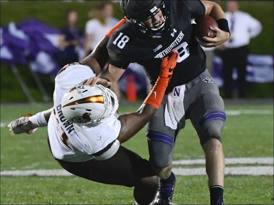 Northwestern quarterback Clayton Thorson (18) gets tackled by against Bowling Green defensive lineman Malik Brown (51) during Saturday's game in Evanston, Ill.