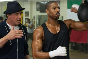 This photo provided by Warner Bros. Pictures shows Michael B. Jordan, right, as Adonis Johnson and Sylvester Stallone as Rocky Balboa in 'Creed.'
