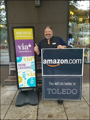 Michael Taylor, a Toledo native, has hung a message for Amazon in his window across the street from the online retail giant's headquarters in Seattle.