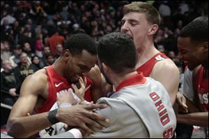 Ohio State forward Keita Bates-Diop, left, celebrates with teammates Andrew Dakich, right, and Joey Lane after defeating Purdue 64-63.
