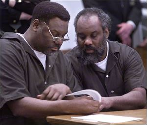 Nathaniel and Anthony Cook look over plea bargain paperwork during their sentencing at Lucas County Courthouse on April 6, 2000.