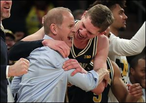 Michigan head coach John Beilein, left, celebrates with Michigan forward Moritz Wagner after Michigan defeated Purdue 75-66 to win the Big Ten Conference tournament championship.