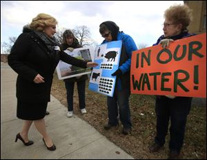 Ohio State Rep. Teresa Fedor (D-Toledo), left, speaks to demonstrators, from left, Kris Moazed, Marilyn Bernstein, and Pat McGlauchlin, during a picket by the Advocates for a Clean Lake Erie outside the Federal Courthouse in Toledo on Tuesday.