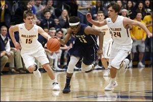 Toledo Christian's Delano Smith, front, tries to dribble away from Edgerton's  Clayton Flegal, left, and Tyson Curry during the Eagles' victory in a Division IV district semifinal at Napoleon High School on Wednesday night.