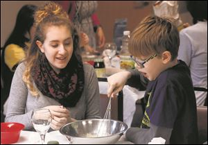 Zoe Kuehn, 15, left, laughs with Cooper Kruse, 10, as they make Hamantashen cookies together in advance of Purim Tuesday, February 13, 2018.
