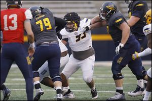 Rossford graduate Nate Childress (93) fights offensive linemen during the University of Toledo football spring game on April 13 at the Glass Bowl.