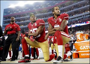 In this 2016 file photo, San Francisco 49ers safety Eric Reid (35) and quarterback Colin Kaepernick (7) kneel during the national anthem before an NFL football game.