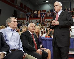Former White House Budget Director Rob Portman, left seated, looks up at Republican presidential candidate, Sen. John McCain as McCain makes a campaign stop in Portsmouth, Ohio in 2008. Mr. Portman is now a U.S. senator.