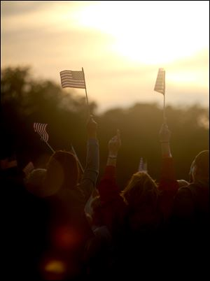 Fans wave American flags as the sun sets during last year's Bash On The Bay country music festival in Put-in-Bay, Ohio.