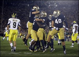 Notre Dame's Nicky Baratti, second from right, is congratulated by teammates after intercepting a pass intended for Michigan's Drew Dileo (9) during the first half of a September, 2012 game in South Bend, Ind.