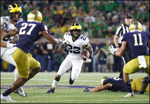 Michigan running back Karan Higdon cuts between Notre Dame cornerback Julian Love and safety Alohi Gilman.