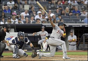 Detroit Tigers pinch hitter Jeimer Candelario, right, strikes out as New York Yankees catcher Gary Sanchez, second from left, looks on,