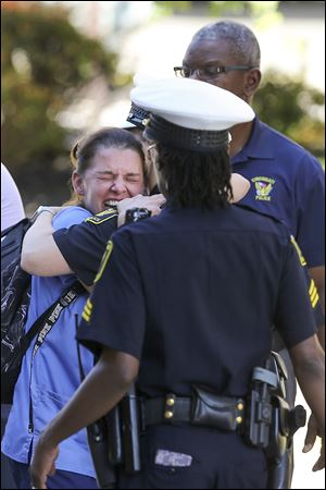 A woman is comforted by authorities after a shooting Thursday in downtown Cincinnati left four people dead.