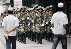 Paramilitary police officers patrol as Uighur men walk by in Urumqi, western China's Xinjiang province, in 2009.