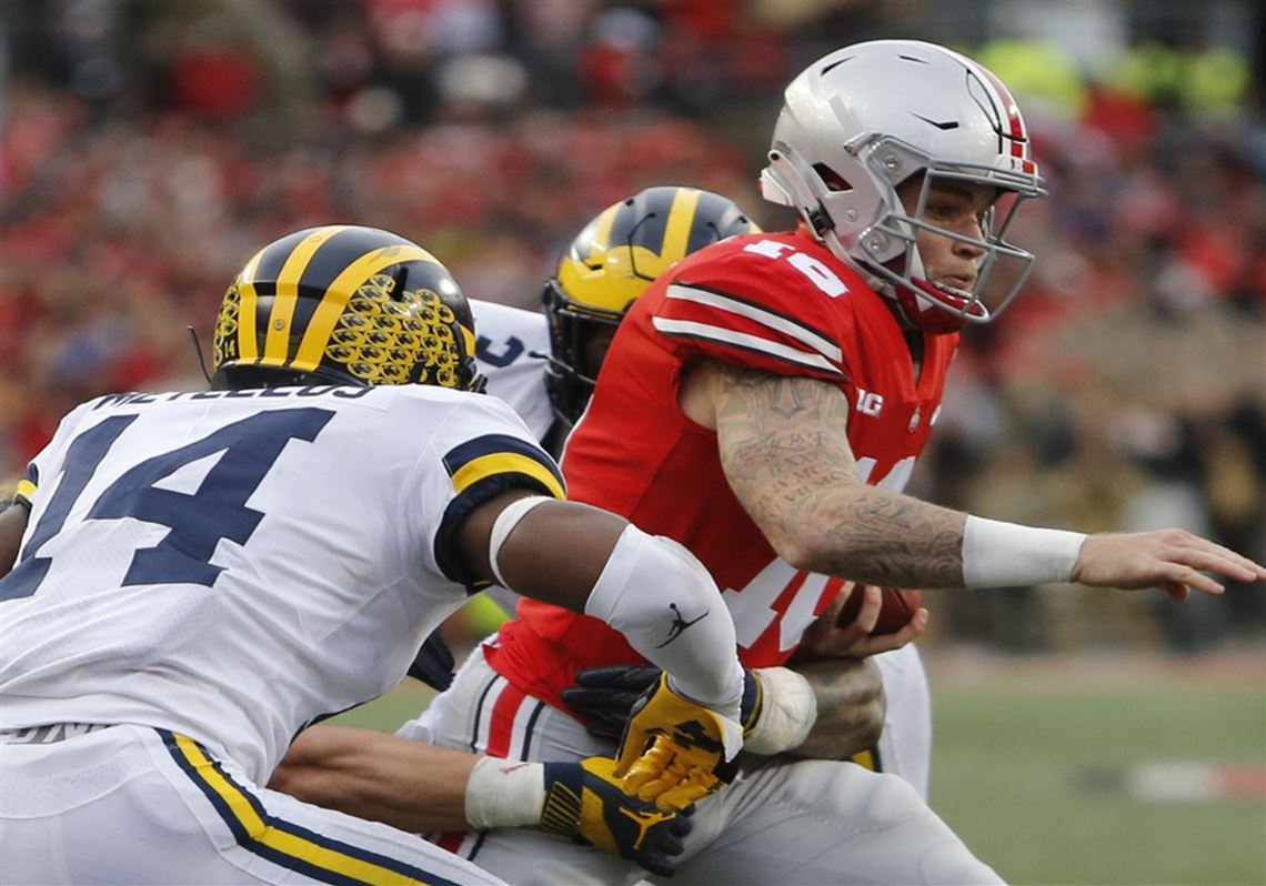 2683c2b4faa Ohio State quarterback Tate Martell, right, is tackled by Michigan  defenders during the second