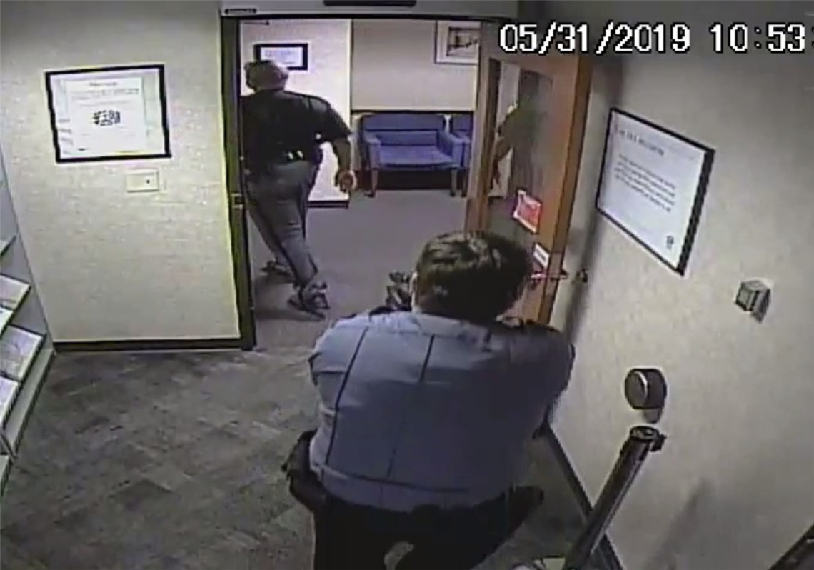 In a frame grab from security camera footage, security guard Seth Eklund is shown with his gun drawn on Lucas County Sheriff